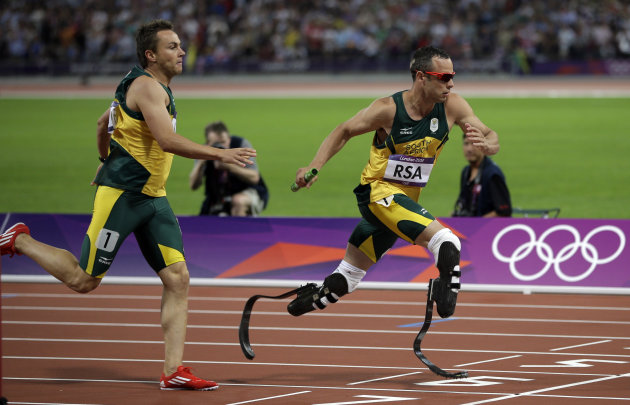 South Africa&#39;s Oscar Pistorius takes the baton from teammate L J van Zyl during the men&#39;s 4x400-meter during the athletics in the Olympic Stadium at the 2012 Summer Olympics, London, Friday, Aug. 10, 2012. (AP Photo/Matt Slocum)