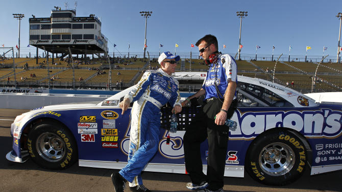 Mark Martin, left, talks with a crew member while leaning on his car after his laps during Sprint Cup qualifying for the NASCAR Subway Fresh Fit 500 auto race on Friday, March 1, 2013, in Avondale, Ariz.  Martin won the pole position for the Sunday race. (AP Photo/Ross D. Franklin)