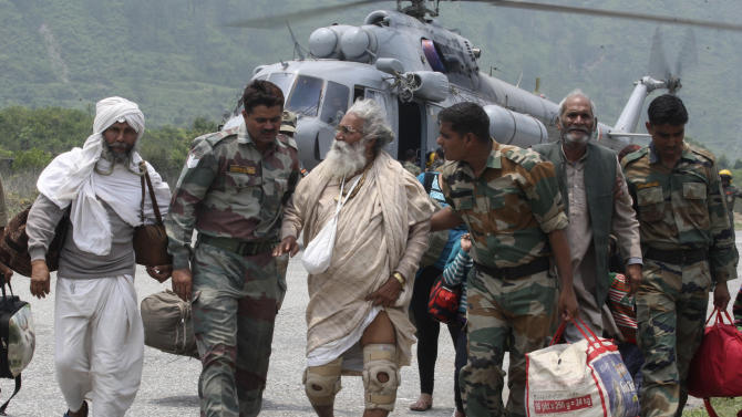 In this Saturday June 22, 2013, photo, Indian army soldiers assist elderly Indian pilgrims to walk towards the safer camps after being evacuated from the higher reaches of mountains in northern Indian state of Uttarakhand. Bad weather was hampering efforts Sunday to evacuate thousands of people stranded in the northern India state of Uttarakhand where nearly 1,000 people have died in monsoon flooding and landslides, army officials said. (AP Photo)