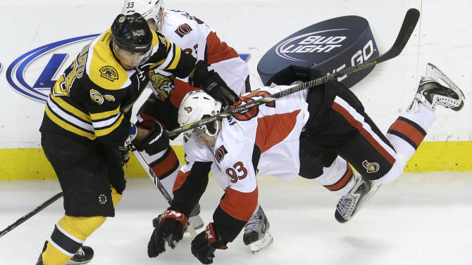 Boston Bruins left wing Brad Marchand (63), left, collides with Ottawa Senators center Mika Zibanejad (93), right, of Sweden, in the first period of an NHL hockey game in Boston, Sunday, April 28, 2013. Senators left wing Jakob Silfverberg, background, skates behind. (AP Photo/Steven Senne)