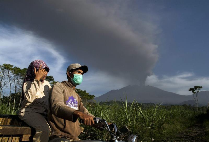 FUL58. Banyuwangi (Indonesia), 12/07/2015.- Residents ride motorcycle near the Mount Raung as its spews volcanic ash at Sumber Arum village in Banyuwangi, East Java, Indonesia, 12 July 2015. A volcanic eruption on Indonesia's Java island has forced the closure of four airports, including those on the popular tourist islands of Bali. Mount Raung, located in East Java province, has been spewing ash and rocks since June, prompting authorities to raise its alert to the second highest level EFE/EPA/FULLY HANDOKO