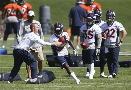 Denver Broncos running back Montee Ball takes a handoff during drills at off season training camp at the NFL football team's training facility in Englewood, Colo., on Monday, May 10, 2013
