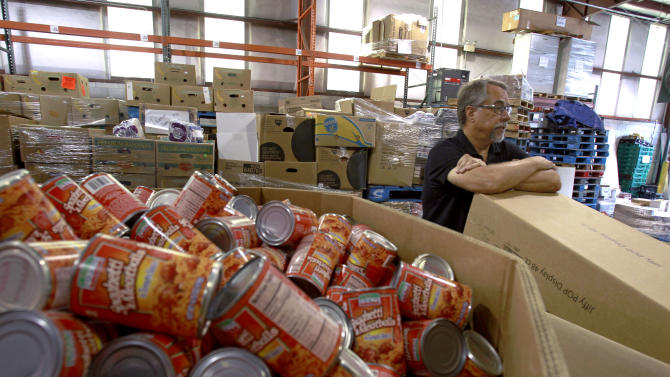 FILE- In this Monday, July 30, 2012 photo, Dave Krepcho, director of the Second Harvest Food Bank, looks over a supply of goods that have arrived at the food bank warehouse in Orlando, Fla. US wholesale businesses boosted stockpiles 0.5 percent in August as sales rose 0.9 percent.(AP Photo/John Raoux, File)