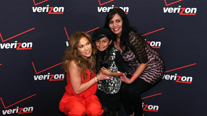 IMAGE DISTRIBUTED FOR VERIZON WIRELESS - Jennifer Lopez poses for a picture with Flyaway Winners at the Verizon Wireless meet Jennifer Lopez Flyaway Contest, on Saturday, Jan. 26, 2013 in Santa Monica, Calif. (Photo by Casey Rodgers/Invision for Verizon Wireless/AP Images)