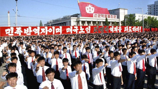 """In this photo released by Korean Central News Agency (KCNA) and distributed by Korea News Service in Tokyo, North Koreans shout slogan during  a massive rally at Kim Il Sung Square in Pyongyang, North Korea, to denounce the conservative government of South Korean President Lee Myung-bak as a """"group of unparalleled traitors"""" Monday, July 4, 2011.  The North's official Korean Central News Agency said Monday that more than 100,000 citizens, soldiers and senior government and army officials flocked to the square.  (AP Photo/Korean Central News Agency via Korea News Service) JAPAN OUT UNTIL 14 DAYS AFTER THE DAY OF TRANSMISSION"""