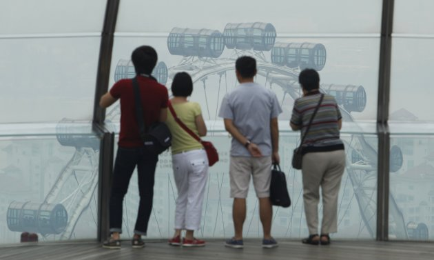 Tourists look at the Singapore Flyer on a hazy day in Singapore