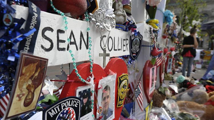 Photographs of slain Massachusetts Institute of Technology campus officer Sean Collier, center, are part of a makeshift memorial near the Boston Marathon finish line in Boston's Copley Square Tuesday, May 7, 2013 in remembrance of the Boston Marathon bombings. Authorities allege that the Boston Marathon bombing suspects were responsible for Colliers death. (AP Photo/Steven Senne)