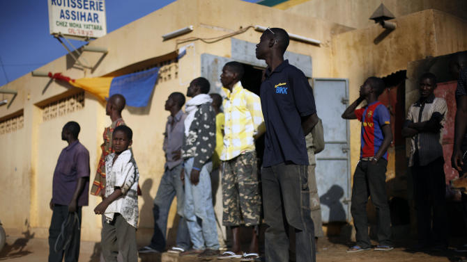 Malian residents watch a French combat helicopter fly over the city during exchanges of fire with jihadists in Gao, northern Mali, Sunday, Feb. 10, 2013. (AP Photo/Jerome Delay)