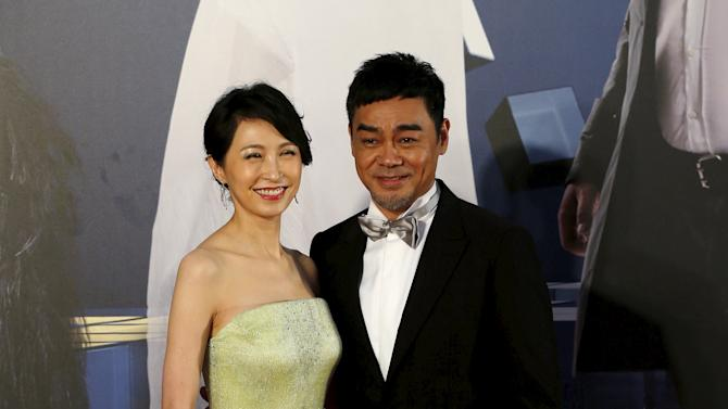Hong Kong actor Sean Lau and his wife, actress Amy Kwok, pose on the red carpet upon their arrival at the Hong Kong Film Awards