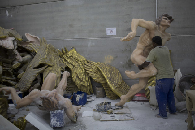 In this photo taken Tuesday, Jan. 22, 2013, a man caries a Carnival float sculpture at the Grande Rio Samba school in Rio de Janeiro, Brazil. Yet it's from warehouses like this one that Rio's over-the