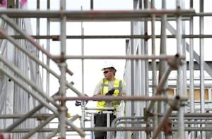 A construction worker assembles metal frames at a housing development project in south London