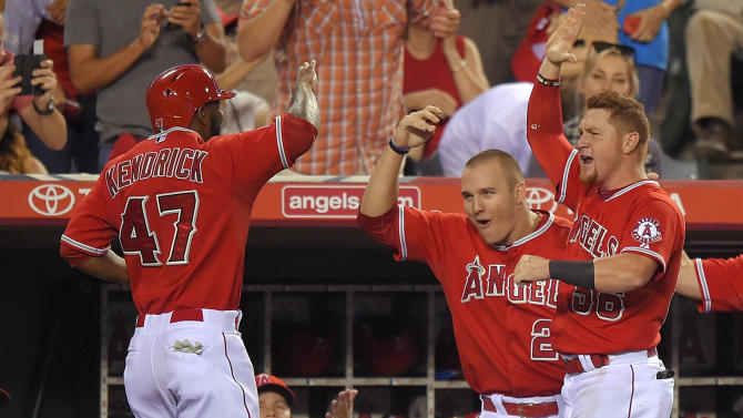 Los Angeles Angels' Mike Trout, center, and Kole Calhoun, right, congratulate Howie Kendrick after he scored on a throwing error by Seattle Mariners right fielder Chris Denorfia during the seventh inning of a baseball game, Wednesday Sept. 17, 2014, in Anaheim, Calif. (AP Photo/Mark J. Terrill)