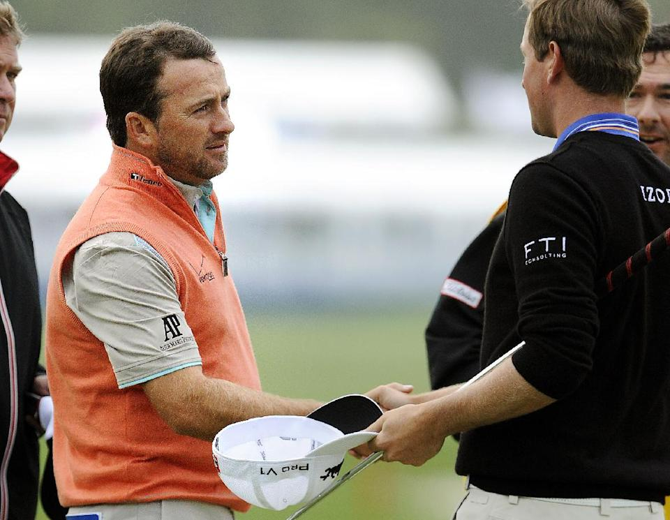 Graeme McDowell, of Northern Ireland, is congratulated by Webb Simpson, right, after winning the RBC Heritage golf tournament in Hilton Head Island, S.C., Sunday, April 21, 2013. McDowell defeated Webb Simpson in a playoff. (AP Photo/Stephen Morton)