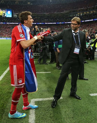 Borussia Dortmund head coach Juergen Klopp, right,  reacts with Bayern's Mario Mandzukic of Croatia, after his team lost the Champions League Final against Bayern Munich, at Wembley Stadium in London,