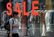 A pedestrian walks in front of a boutique advertising a sale in Tokyo&#39;s Shinjuku shopping district, 2010. A bill to double Japan&#39;s sales tax and partially plug its gaping debt hole cleared its final parliamentary hurdle in a triumph for the prime minister that could ultimately also cost him his job