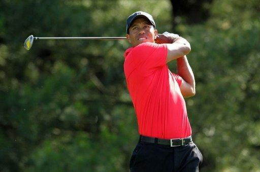 Tiger Woods blasted out of the rough for a 48-foot chip-in birdie on the par-3 16th hole to seize a share of the lead