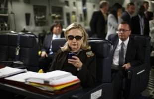 U.S. Secretary of State Hillary Rodham Clinton works from a desk inside a C-17 military plane en route to Libya in october 2011. (Photo: Kevin Lamarque/AP/ Pool)