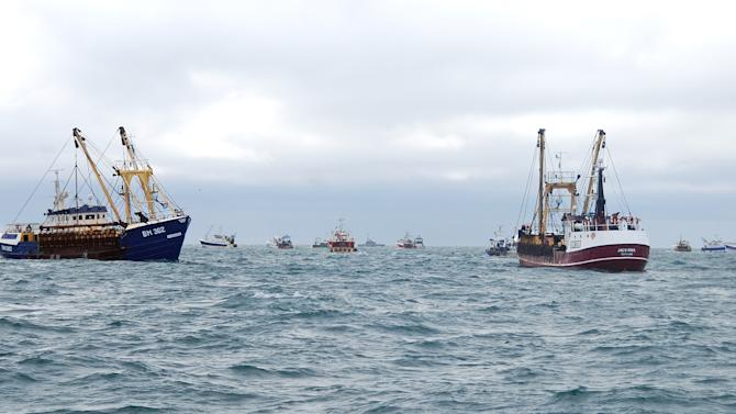 This Oct. 8, 2012 photo shows, British fish boats, left  and right,  being prevented to fish by French fishermen, small boats in background, in the English Channel, off Le Havre, western France. A bumper season for the French national dish of Coquilles St. Jacques has turned into a bitter dispute in the English Channel, as French fishermen angry over British expansion into their waters surrounded British boats in a show of maritime force.(AP Photo/Pierre Guillaume)