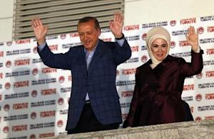 Turkey's Prime Minister Erdogan and wife Ermine wave hands to supporters as they celebrate his election victory in front of the party headquarters in Ankara