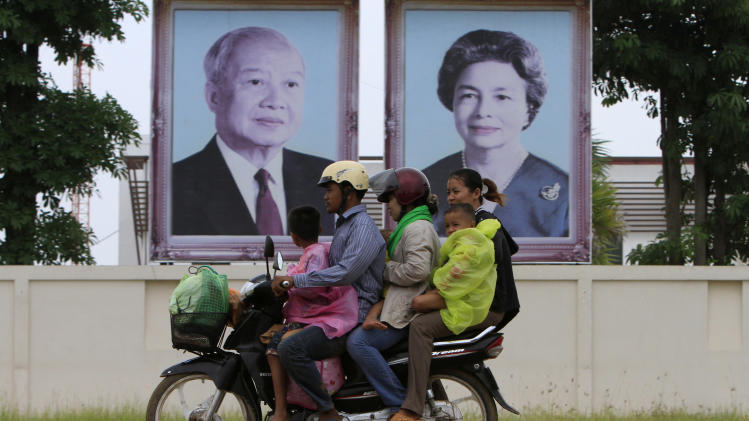 A Cambodian family members ride on a motorbike as they head back from their home village, passing by portraits of former King Norodom Sihanouk, left, and his wife Queen Monineath, Monday, Oct.15, 2012, at the outskirt of Phnom Penh, Cambodia. Sihanouk, the revered former king who was a towering figure in Cambodian politics through a half-century of war, genocide and upheaval, died Monday. He was 89. (AP Photo/Heng Sinith)