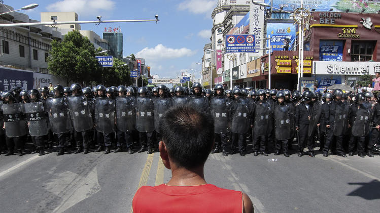 A protester stands in front of a lines of riot police officers Saturday July 28, 2012 in Qidong, Jiangsu Province,  China.  Authorities in eastern China dropped plans for a water-discharge project Saturday after thousands of protesters angry about pollution took to the streets, in the latest of many such confrontations in a country where three decades of rapid economic expansion have come at an environmental price. (AP Photo/Eugene Hoshiko)
