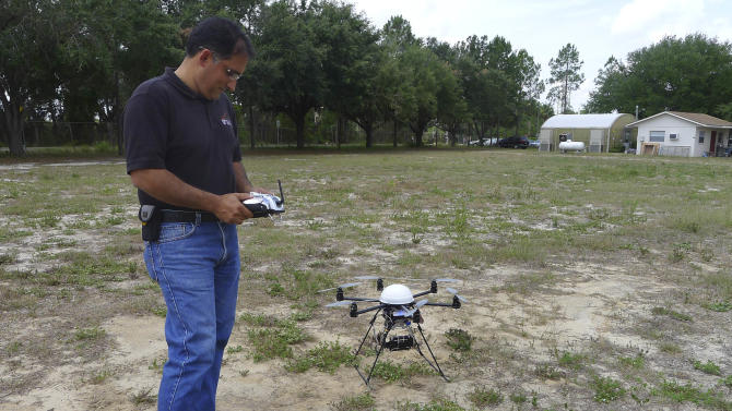 In this photo taken June 9, 2011 in Lake Alfred, Fla., University of Florida citrus researcher Reza Ehsani stands near a remote control helicopter. The device is fitted with a camera and is used to monitor crops from the air. (AP Photo/Tamara Lush)