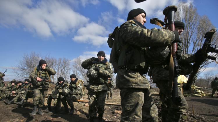 Ukrainian border guards prepare for a training session at a military camp in the village of Alekseyevka on the Ukrainian-Russian border, eastern Ukraine, Friday, March 21, 2014. Russian President Vladimir Putin signed bills on Friday making Crimea part of Russia, completing the annexation from Ukraine. (AP Photo/Sergei Grits)