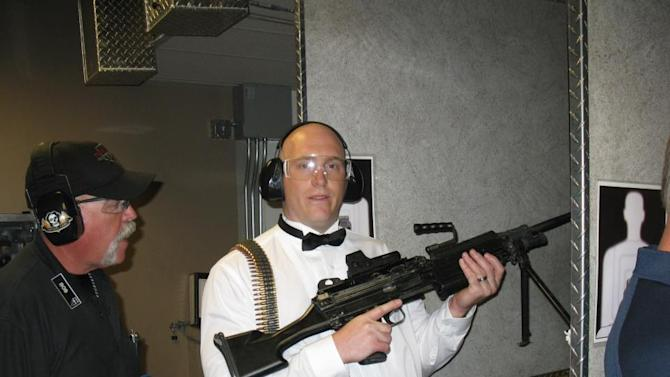 "This July 28, 2012 photo provided by Bob MacDuff shows MacDuff holding an automatic weapon at the Gun store in Las Vegas after his ""shotgun wedding."" One Las Vegas shooting range is selling ""take a shot at love"" packages that include 50 submachine gun rounds. Another is offering wedding packages in which the bride and groom can pose with Uzis and ammunition belts. And a third invites lovebirds to renew their vows and shoot a paper cutout zombie in the face. (AP Photo/Bob MacDuff)"