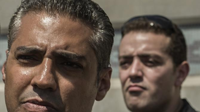 Al-Jazeera journalists, Canadian Mohamed Fahmy (L) and Egyptian Baher Mohamed, wait outside Cairo's Torah prison on July 30, 2015 where their trial was due to take place