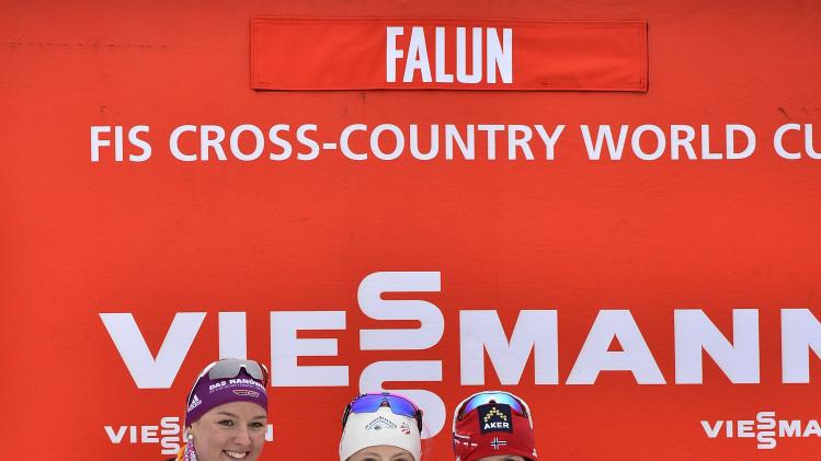 U.S. Kikkan Randall, centre, holds the trophy after winning the FIS sprint World Cup cross country ski in Falun, Sweden, Friday March 14, 2014. Runner up Denise Herrman, Germany, to the left and third placed Marit Bjorgen, Norway, to the right. (AP photo / Anders Wiklund) SWEDEN OUT