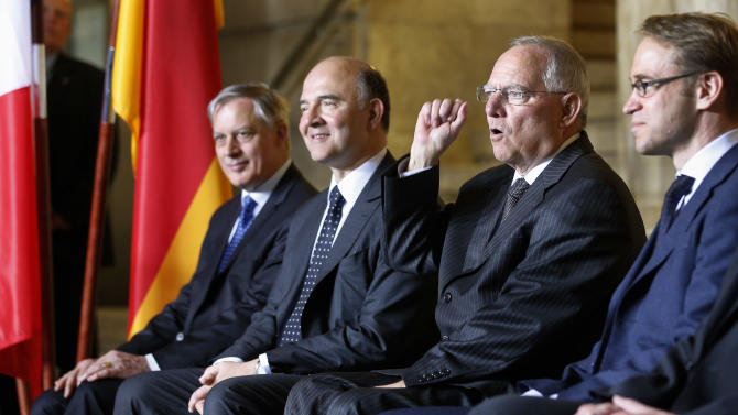 German Finance Minister Wolfgang Schaeuble, second right, lifts a fist as he poses for a family photo with his counterpart from France, Pierre Moscovici, second left, the President of the Federal Bank of France, Christian Noyer, left, and the President of the German Federal Bank, Jens Weidmann, right, as part of the 25th meeting of the German French Finance and Economy Council in Berlin, Germany, Tuesday, May 7, 2013. (AP Photo/Michael Sohn)