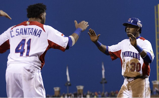 The Dominican Republic's Alejandro De Aza (30) is congratulated by Carlos Santana after scoring against Puerto Rico during the fifth inning of the championship game of the World Baseball Classic in Sa