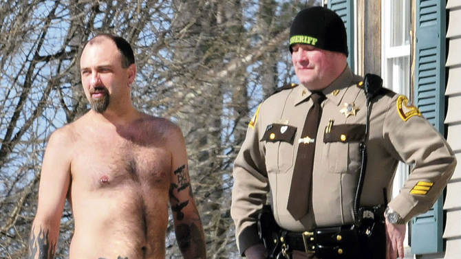 """In this Tuesday, March 18, 2014 photo, Michael Smith, left, stands beside a Somerset County Sheriff deputy outside his home in Norridgewock, Maine. Officers armed with assault rifles descended on Smith's home after members of a tree removal crew he'd told to clear off his property reported that he had a gun. The """"gun"""" the tree crew had seen on Smith actually was a life-sized tattoo of a handgun on his stomach. (AP Photo/Morning Sentinel, David Leaming)"""