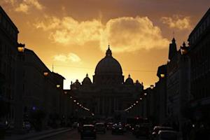 Saint Peter's Basilica at the Vatican is silhouetted during sunset in Rome