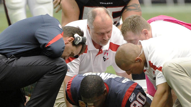 Houston Texans coach Gary Kubiak, left, and trainers check on wide receiver Andre Johnson (80) after he was hurt in the second quarter against the Pittsburgh Steelers in an NFL football game Sunday, Oct. 2, 2011, in Houston. (AP Photo/Dave Einsel)