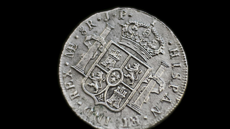 A silver coin from the shipwreck of a 1804 galleon, on its first display to the media at a ministry building, in Madrid, Friday, Nov. 30, 2012. Spanish cultural officials have allowed the first peep at 16 tons (14.5 metric tons) of the shipwreck, 'Nuestra Senora de las Mercedes' a treasure worth an estimated $500 million that a U.S. salvage company gave up after a five-year international ownership dispute. (AP Photo/Daniel Ochoa de Olza)