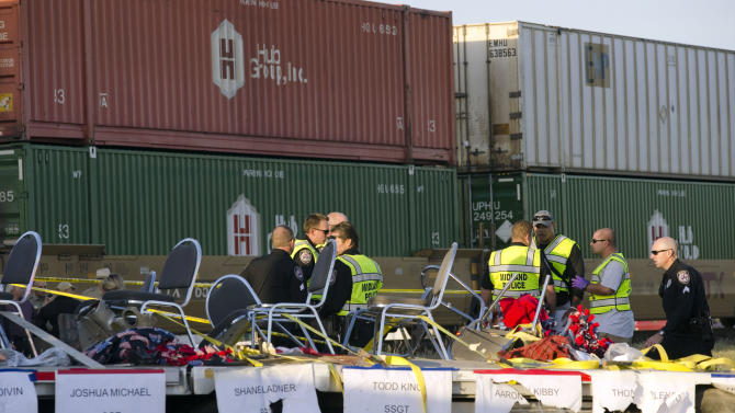 """Midland police, fire and sheriffs respond to an accident where a trailer carrying veterans in a parade was struck by a train crossing in Midland, Texas, Thursday, Nov. 15, 2012. """"Show of Support"""" president and founder Terry Johnson tells the Midland Reporter-Telegram that a Union Pacific train slammed into the trailer that was on its way to a wounded veterans event, resulting in multiple injuries. (AP Photo/Reporter-Telegram, Tim Fischer)"""