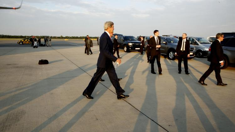 U.S. Secretary of Kerry walks across the tarmac at Vienna International Airport