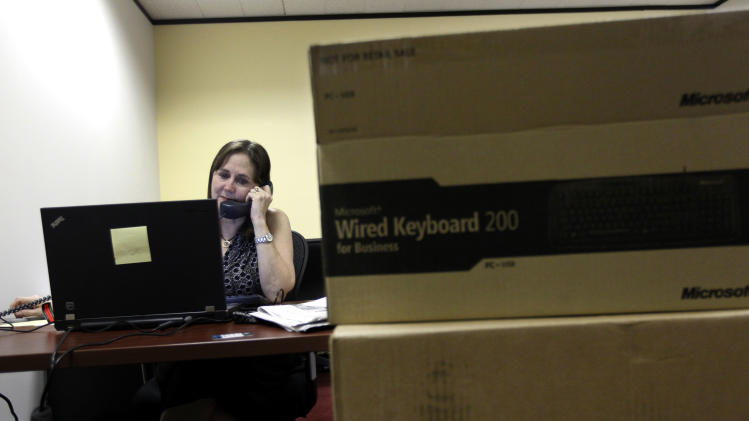 Sara Pagones, left, bureau chief of the new Baton Rouge Advocate New Orleans bureau talks on the phone with computer boxes in the foreground in their  temporary workspace in New Orleans, Thursday, Sept. 27, 2012.  As The Times-Picayune in New Orleans scales back its print edition to three days a week, the Baton Rouge newspaper is starting its own daily edition to try to fill the void. The move by The Advocate sets up an old-fashioned newspaper competition, even as more and more people get their news online and from cellphones. (AP Photo/Gerald Herbert)