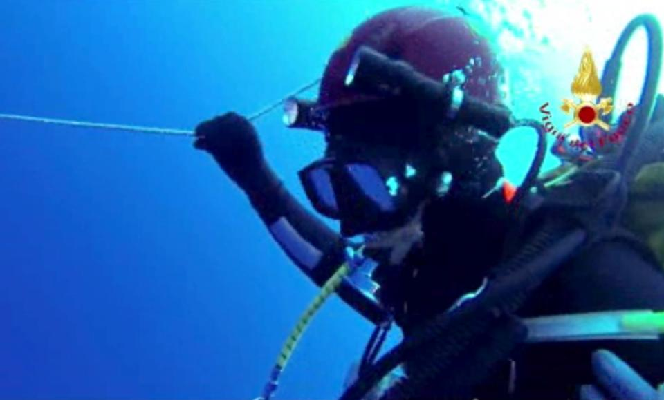 In this image made from video provided by Italian Firefighters, a diver grabs a rope underwater, Friday, Oct. 4, 2013, as efforts continue to reach a boat underwater that was transporting hundreds of migrants before catching fire and sinking off the Sicilian island of Lampedusa, Italy, on Thursday. (AP Photo/Italian Firefighters)