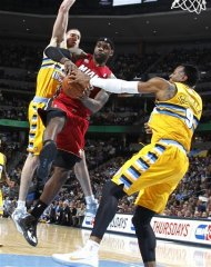 Miami Heat forward LeBron James, center, is tied up as he drives the lane for a shot by Denver Nuggets center Kosta Koufos, left, and forward Andre Iguodala in the first quarter of an NBA basketball game in Denver on Thursday, Nov. 15, 2012. (AP Photo/David Zalubowski)