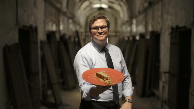 """In this Friday, May 31, 2013 photo, director of public programming, Sean kelly displays a plate of Nutraloaf, presently served in Pennsylvania prisons as a """"behavior modified meal,"""" at Eastern State Penitentiary in Philadelphia. The historic penitentiary plans to serve visitors sample meals from the 1800s, 1900s and today on June 8th and 9th. (AP Photo/Matt Rourke)"""