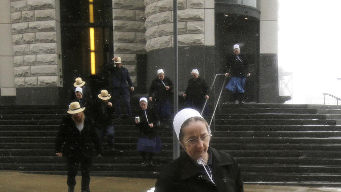 An Amish woman leaves the U.S. Federal courthouse Friday, Feb. 8, 2013, in Cleveland. The ringleader in a series of unusual hair- and beard-cutting attacks on fellow Amish religious followers in the U.S. was sentenced Friday to 15 years in prison.  Sam Mullet Sr., 67, the ringleader in a series of unusual hair- and beard-cutting attacks on fellow Amish religious followers in the U.S. was sentenced Friday to 15 years in prison, and 15 family members received sentences of one year to seven years. The defendants were charged with a hate crime because prosecutors believe religious differences brought about the attacks.  (AP Photo/Tony Dejak)