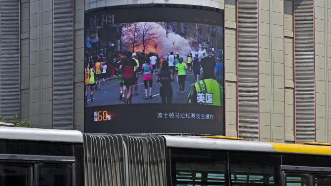 Commuters on a bus pass bt a huge screen which reports Boston's marathon bombings that killed three and wounded more than 170 people, in Beijing, China Wednesday, April 17, 2013. A state-run Chinese newspaper says the third person killed in the Boston Marathon bombings is a Chinese graduate student at Boston University originally from China's northeastern city of Shenyang. (AP Photo/Andy Wong)