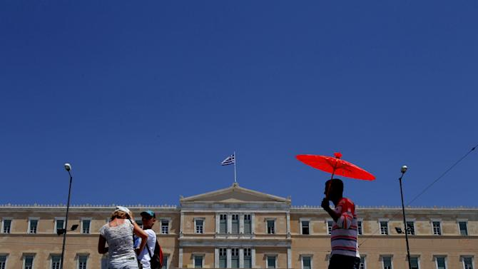A couple of tourist, left, stand in front of a Greek parliament as another person, right, sells umbrellas at Syntagma square in Athens, Tuesday, June 12, 2012. Greece faces crucial national elections on Sunday, that could ultimately determine whether the debt-saddled, recession bound country remains in the eurozone. First elections on May 6 resulted in a hung parliament. (AP Photo/Petros Karadjias)
