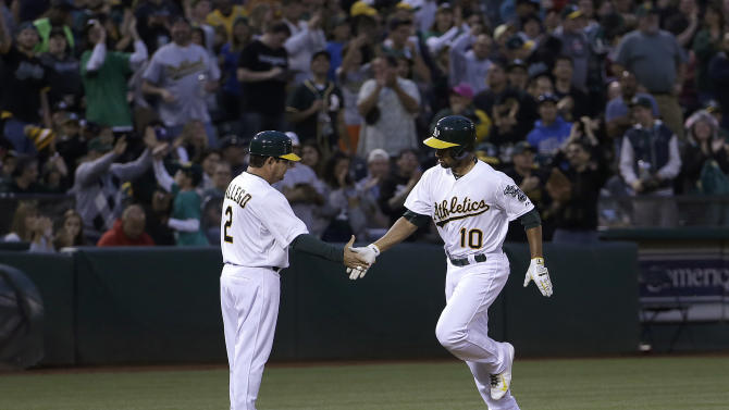 Oakland Athletics' Marcus Semien, right, is congratulated by third base coach Mike Gallego after hitting a solo home run off of Seattle Mariners pitcher Roenis Elias during the fifth inning of a baseball game in Oakland, Calif., Thursday, July 2, 2015. (AP Photo/Jeff Chiu)