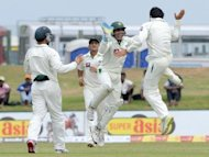 Pakistan&#39;s Saeed Ajmal (right) celebrates with wicketkeeper Adnan Akmal (2nd right) after the dismissal of Sri Lanka&#39;s Tharanga Paranavitana during the first day of the opening Test match at the Galle International Stadium. Tillakaratne Dilshan and Kumar Sangakkara have hammered centuries as Sri Lanka walloped Pakistan on the opening day of the first cricket Test in Galle