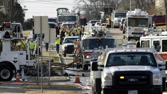 Law enforcement officials, city, gas company and local fire fighters occupy the street in front of a structure that exploded earlier Friday, Jan. 11, 2013, in Lewisville, Texas. An explosion Friday in a North Texas neighborhood leveled a home that is part of a local nonprofit's affordable housing program, injuring at least three men and scattering debris.(AP Photo/Tony Gutierrez)