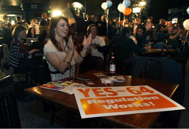 FILE - In this Nov. 6, 2012 file photo, Amanda Jetter celebrates along with others attending an Amendment 64 watch party in a bar after a local television station announced the marijuana amendment's p
