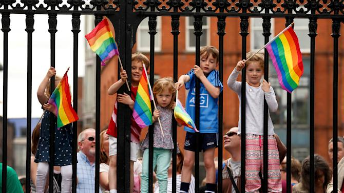 Children wave rainbow flags as they stand with their same-sex marriage supporting parents at Dublin Castle in Dublin